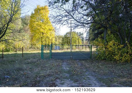 Gate with a gate in a fence on autumn tree background