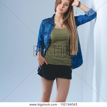 Full lenght a young woman standing near wall .