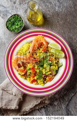 Spanish Paella With Seafood On The Red Teralke With Lime Olive O