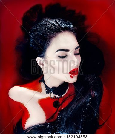 Beauty Halloween Sexy Vampire Woman with dripping blood on her mouth lying in a bath full of blood. Vampire Fashion Art design scene, glamour female vampire girl in bloody bath. Desire, thirst concept