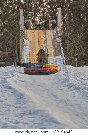 Happy teenager girl on a fast Sleigh Ride down the icy slope