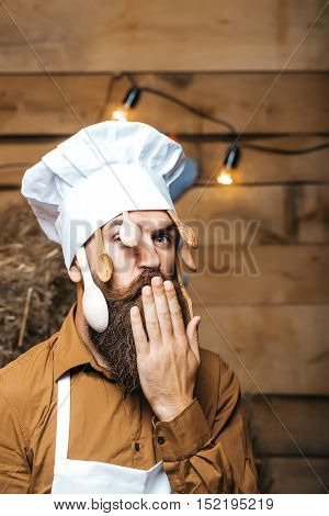 Funny man chef cook or baker with beard and moustache in hat toque with wooden spoons and hand near mouth stands on straw bales on rustic background