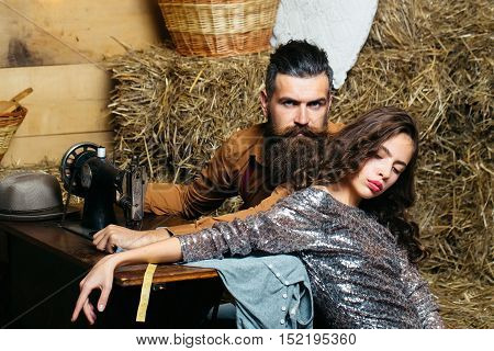 Bearded man tailor or dressmaker and pretty girl customer or sexy model with curly brunette hair in dress pose near vintage sewing machine in rustic workshop