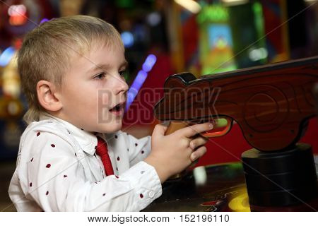 Child shooting a gun in an amusement park