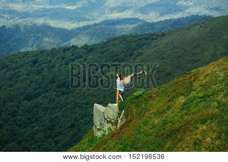 Pretty girl slim sexy model with long hair in dress with blanket stands on in summer on mountains covered with forest and green grass