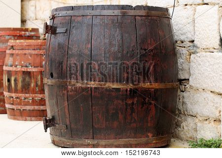 Wine barrels traditional oak wood casks tierces hogsheads coopered wooden containers closed with corks on stone wall background
