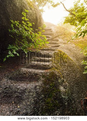 Irregular natural steps carved in the granite rock. Way to the summit illuminated by the sun.
