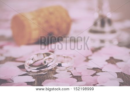 Wedding Rings On A Wooden Background With Confetti Vintage Retro Filter.