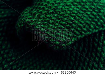 Green woolen knitted fabric texture macro close up