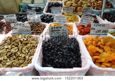 Grodno, Belarus - September 8, 2016: Raisins dried apricots walnuts and other dry fruits on the counter with price tags on the market.