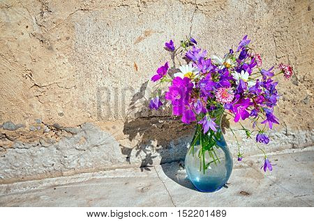 Bouquet Of Wild Flowers - Bluebells, Daisies, Clover Against The Background Of A Concrete Wall With