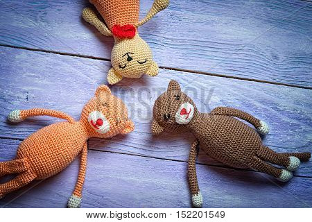 Three Croched Toys Laying On A Wooden Background Top View. Copy Space.