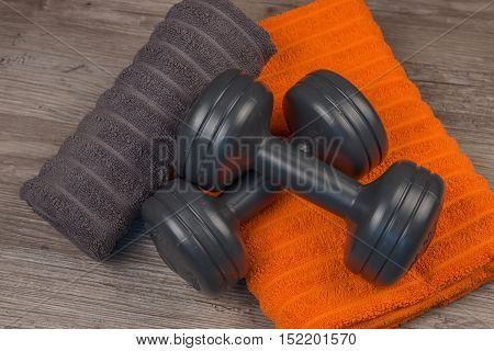 Dumbbell and towel on wooden background, Fitness equipment