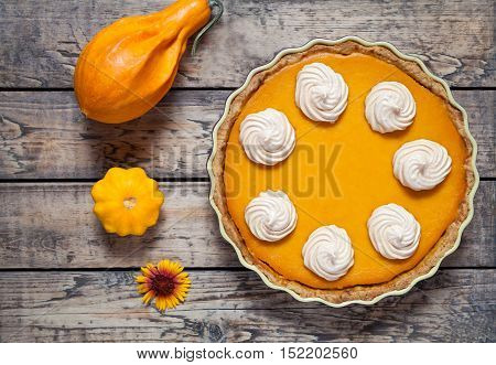 Festive Homemade Delicious Pumpkin pie with whipped cream made for Thanksgiving and halloween, top view. Autumn creative composition.