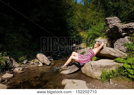 Beautiful young woman resting in the river in Mlodow Glebokie Rytro area Beskid mountains in Poland. Autumn landscape photo.
