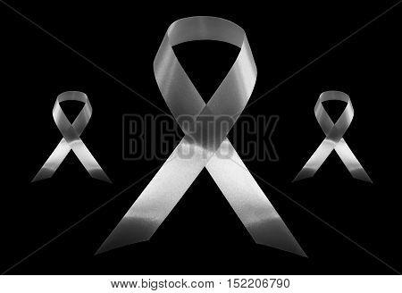 Black awareness ribbon, Mourning and melanoma symbol, isolated on black background