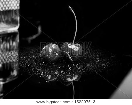 Two juicy fresh wet cherries with grey filter
