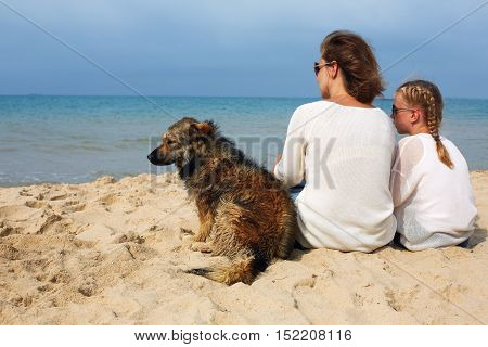 Mom and daughter sit hugging on the sea and look at the water. Near them sits their small dog.