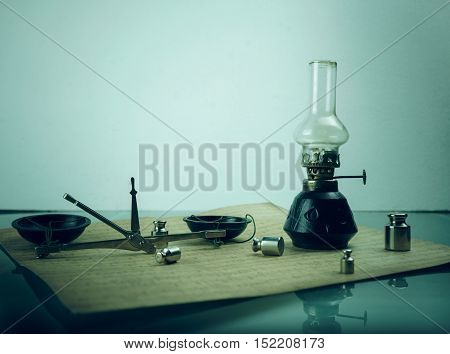 scales with weights, a kerosene lamp. space for text