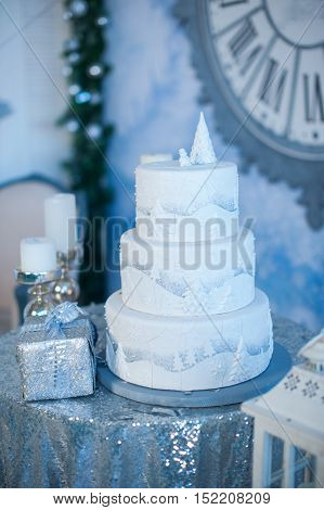 three-layer white holiday cake on the table decorated with fir trees and gift box.
