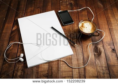 Blank paperwork template. Responsive design mock up on vintage wooden background. Paper letterhead coffee cup smartphone pencil and headphones. Top view.