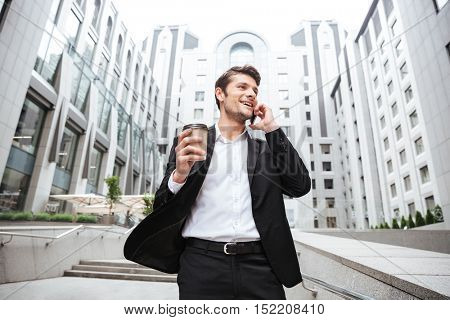 Happy young businessman talking on mobile phone and drinking coffee near business center