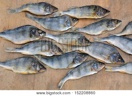 Many dried perch on a wooden background. River fish close up.