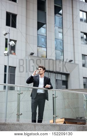 Serious young businessman standing and drinking coffee near business center