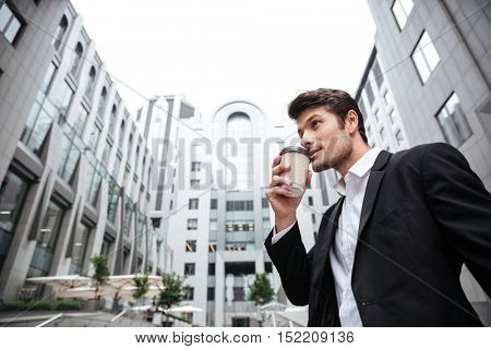 Handsome young businessman standing and drinking take away coffee near business center