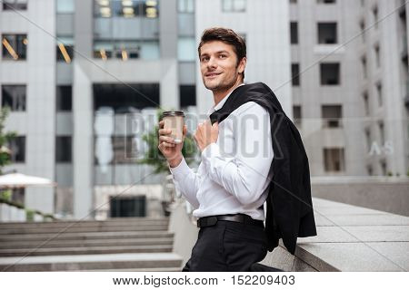 Happy young businessman standing and drinking coffee in the city