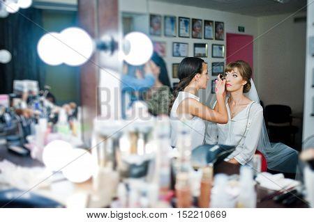 Wedding Makeup Artist  In Short Sexy Denim Shorts Making A Make Up For Bride.