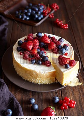 Homemade Creamy mascarpone cheesecake with berries forest fruits and strawberries on dark wooden table. Cream mousse cake.