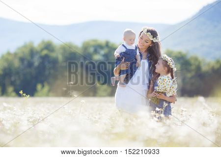 Happy family of three,mother,older sister and little brother spend time together in the highlands on a field of blooming white daisies in summer in the fresh air,mother and daughter wearing wreaths of flowers-white daisies