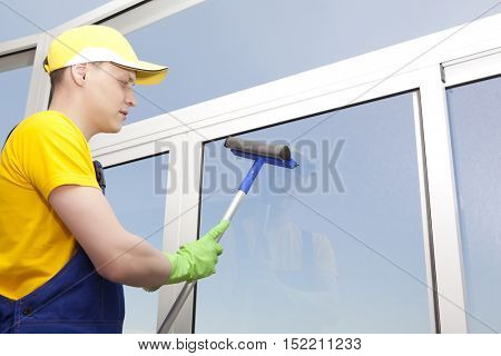 Professional cleaning. Young man washes window