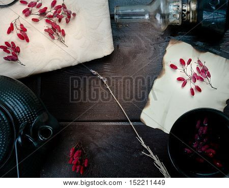 barberry berries, kerosene lamp and a kettle on the wooden background
