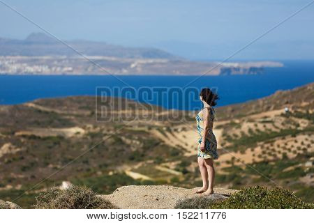 Woman admiring the sea view standing on a high mountain of Crete in Greece