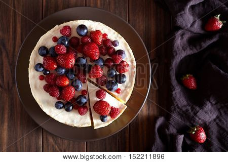 Close up. Delicious Homemade creamy mascarpone New York Cheesecake with berries on dark wooden table. Top viev.