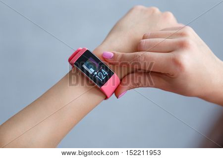 Isolated female hand with pink smartwatch taking pulse after exercising indoor on a light and blured background