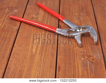 Metal plumber wrench with red handles on wooden brown surface