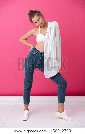 Full length portrait of a beautiful young woman in casual clothes holding shirt on her shoulder isolated on the pink background