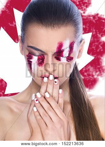 Beautiful young female face with bright fashion multicolored make-up and beauty purple manicure of fingernails