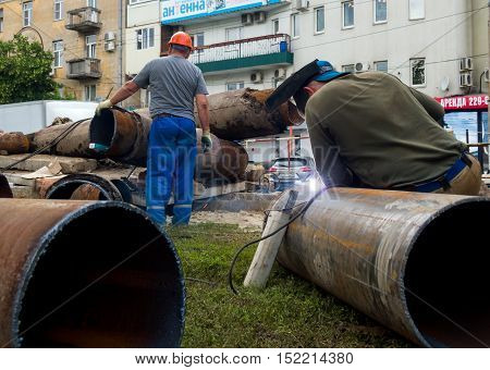 Voronezh, Russia - June 16, 2016: Workers changing mains pipe heat supply in the city of Voronezh