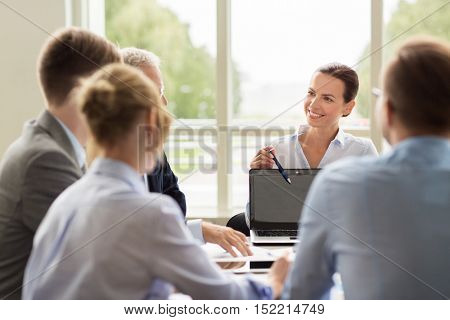 business, people and technology concept - business team with laptop computer meeting in office