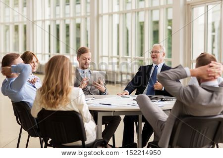 business, people and technology concept - business team with tablet pc , laptop computer and papers on table meeting at office