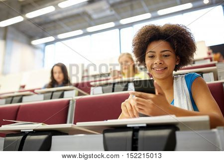 education, high school, university, learning and people concept - african student girl with smartphone at lecture