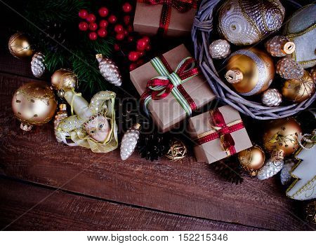 Christmas or New Year background: fur-tree, branches, gifts, colored glass balls, decoration and cones on wooden background