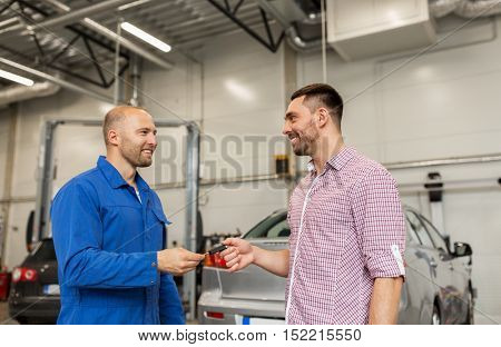 auto service, repair, maintenance and people concept - mechanic with clipboard giving key to happy smiling man or owner at car shop