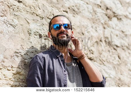 people, music, technology, leisure and lifestyle - hipster man with earphones on city street listening to music