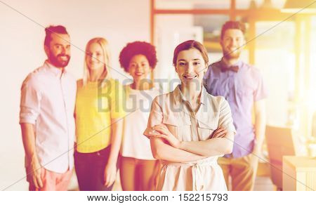 business, startup, people and teamwork concept - happy young woman over creative team in office