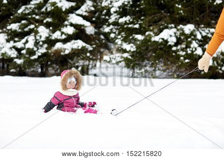 childhood, sledding, fashion, season and people concept - happy little kid riding on sled outdoors in winter